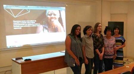 Defesa de trabalho de conclusão de curso de Caroline Loppi: membros da banca e Caroline com projeção do site Mundo Prateado atrás delas.