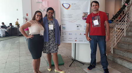 Representantes do NAU no IHC 2017. Carolina, Priscyla e Bruno em frente ao banner do IHC17 no hall de entrada do evento