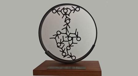 Troféu com base em madeira e um circulo de ferro. Dentro do círculo o desenho de um mapa com parte da América do Norte e a América do Sul em destaque. O mapa é formado por bonecos de mãos dadas.